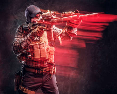 Special forces soldier wearing a checkered shirt and protective equipment holding an assault rifle and aim at the enemy. Red light effect in motion. Studio photo against a dark textured wall Banco de Imagens