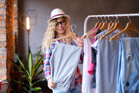 Happy young woman in hat and glasses is tidy up in her wardrobe for summer at modern loft. She wear checkered shirt. Lamp at background. Фото со стока - 121345223