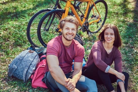An attractive couple sitting on the ground, relax after biking in the park.
