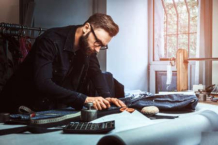Schneiderin misst Stoff mit Meter in seinem Studio. Er trägt Jeans und Brille. Im Hintergrund gibt es viele Nähwerkzeuge.