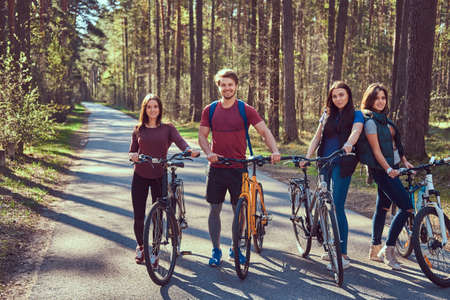 Active friends walk with bike at forest road in spring. Reklamní fotografie - 121345399