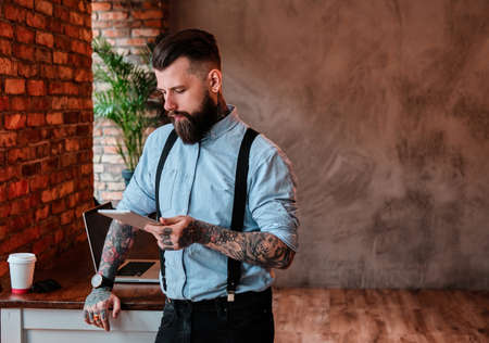 Serious bearded man is leaning on the table. He is wearing shirt and suspender. He has tattoes on his arms and neck. He is holding tablet and read something from it.