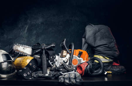 Safety unform on the table -  boots, helmet and gloves with oxygen cylinder, hammer respirator and chainsaw. There are dark background.