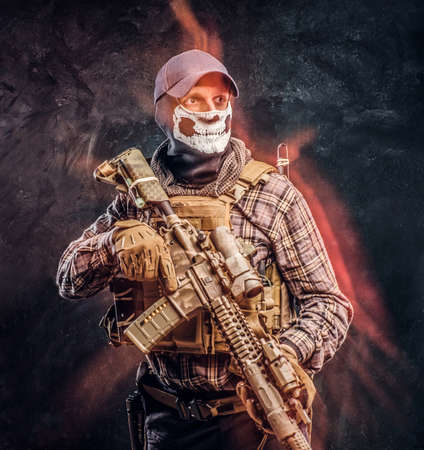 Private security service contractor wearing a balaclava skull and cap holding an assault. Red light effect. Studio photo against a dark textured wall Banco de Imagens