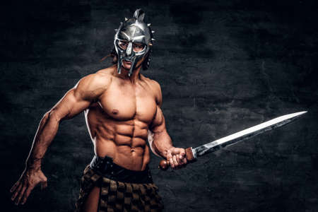 Strong gladiator with sword in his hands. He is wearing gladiators bandage and helmet. Stock Photo