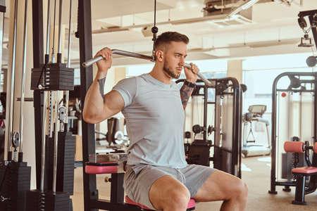 Joven tatuado está haciendo ejercicio para la espalda en aparatos de entrenamiento en el gimnasio.