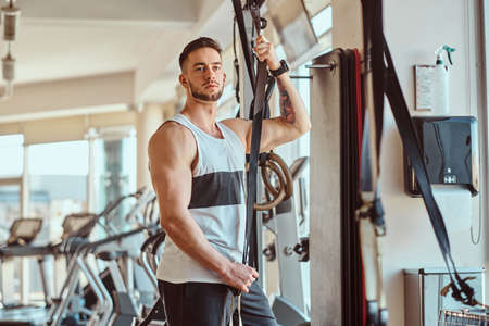 Attractive young bodybuilder is posing next to training apparatus at sunny gym.