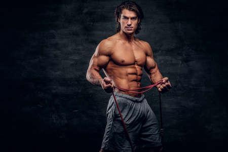 Hombre musculoso atractivo está mirando a la cámara mientras hace estiramientos con goma. Foto de archivo