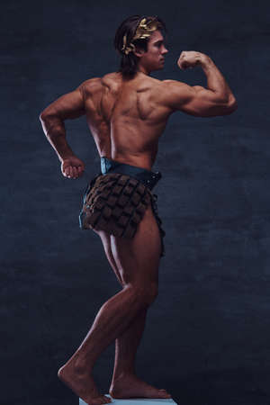 Attractive young bodybuilder is posing on pedestal. He is wearing wreath and bandage.