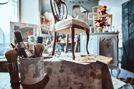 Artists workshop with necessary eguipment like paint, brushes, frames, flowers, table, chair and cupboard. Imagens