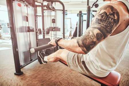Young muscular man with tattoes is doing exercises on the rowing machine in the gym.