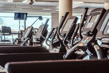 Photo of empty treadmills in gym. There are screen at background. Stock Photo