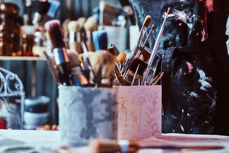 Brushes and jars in artists studio on the table.