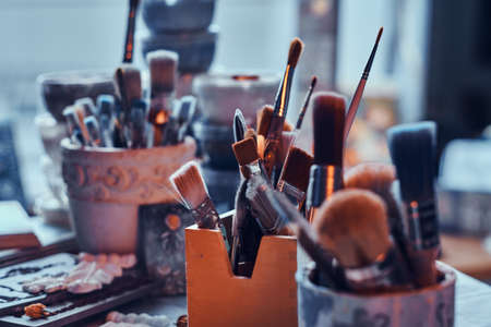 A lot of different brushes on artists table in jars. There are artisticks mess on the table.