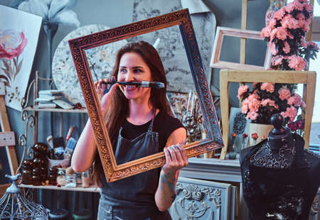 Pretty funny artist is posing with frame and brush in cozy art studio.