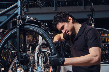 Diligent young mechanic is repairing customers bicycle at workplace.