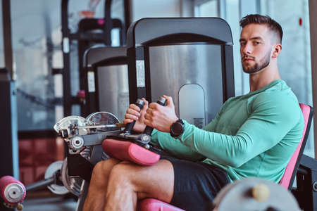 Strong pensive man is sitting on training apparatus in gym and doing legs exercises. Banque d'images