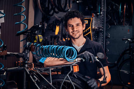 Handsome talented master is fixing bicycle at his own workshop using pneumatic tool. Stock Photo