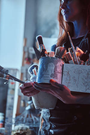 Young painter is tidying up after long working day. She is holding jars with brushes. Imagens