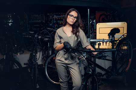Hardworking attractive woman is posing with bicycle at workshop. Imagens