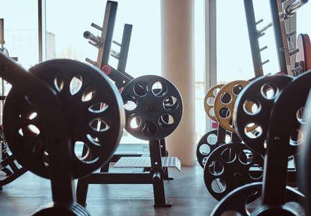 Foto des leeren sonnigen Fitnessstudios voller verschiedener Sportgeräte. Standard-Bild