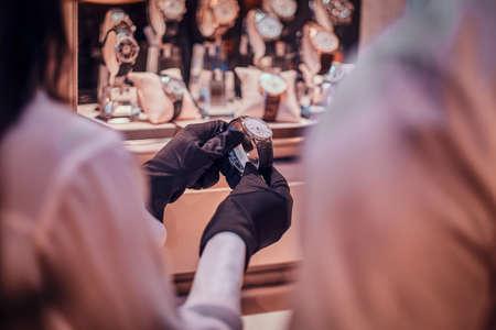 Asistente de tienda con guantes negros está mostrando un reloj caro para un cliente. Foto de archivo