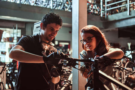 Young master and his attractive apprentice are fixing customers bicycle at workshop. Stock Photo