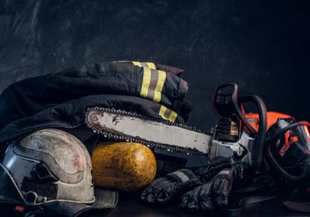 Safety gear, jacket, oxygen cylinder and chainsaw on the table. There are dark background.