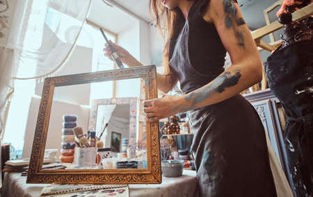 Young talented painter is restourating old frame in her own workshop.