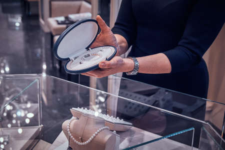 Elegant jewellery shops assistant is showing beautiful pearl necklace in case for customer.
