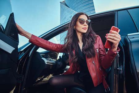 美丽的聪明的妇女摆在她的新的汽车,当聊天在手机时。她穿着红色皮夹克和太阳镜。