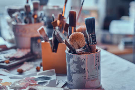 A lot of different brushes on artists table in jars. There are artisticks mess on the table. Фото со стока