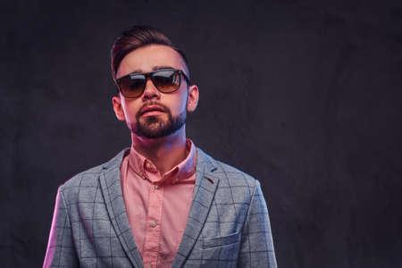 Portrait of styilish proud man in checkered blazer, pink shirt and sunglasses. Stock Photo