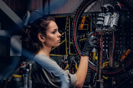 Young beautiful woman is repairing bicycle at busy workshop between pneumatic wires.