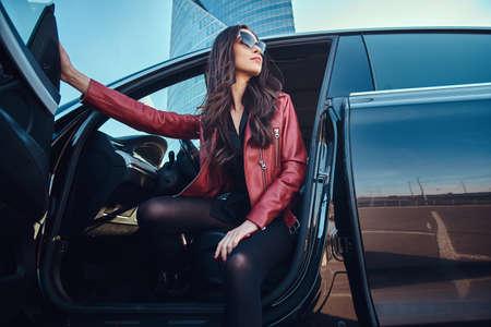 Mujeres atractivas jóvenes está planteando en su coche nuevo. Lleva chaqueta roja y gafas de sol. Foto de archivo