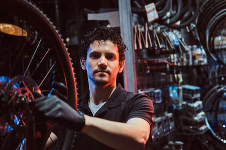 Handsome diligent master is fixing bicycles wheel at his workplace.