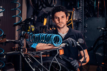 Handsome talented master is fixing bicycle at his own workshop using pneumatic tool. Stock Photo - 122627445