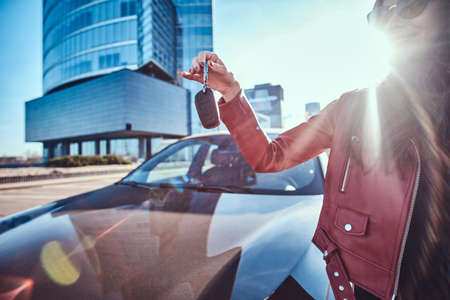 Happy young woman just got keys from her new car, which is behide. There are bright sunny day. Woman is wearing red jacket and sunglasses.