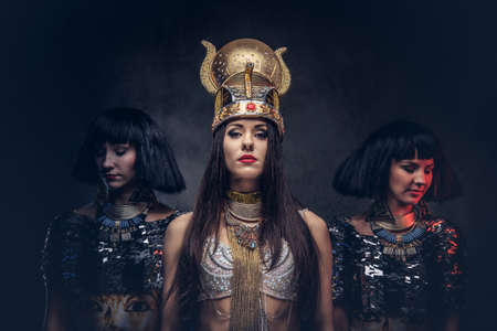 Portrait of haughty Egyptian queen in an ancient pharaoh costume with two concubines. Isolated on a dark background. 版權商用圖片