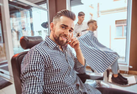 Attractive groomed man is sitting while waiting for a barber at busy barbershop. He is wearing checkered shirt.