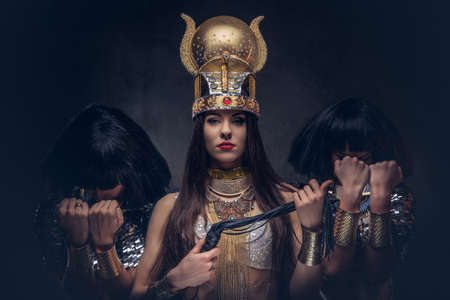 Portrait of haughty Egyptian queen in an ancient pharaoh costume with two concubines. Isolated on a dark background. Standard-Bild