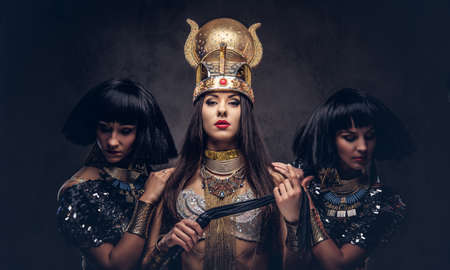 Portrait of haughty Egyptian queen in an ancient pharaoh costume with two concubines. Isolated on a dark background.