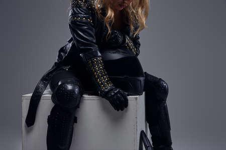 Cropped image of a biker girl wearing motorcycle gear sitting on a gray box in a studio. Reklamní fotografie