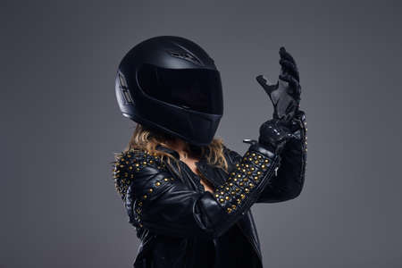 Portrait of a biker girl wearing leather racer costume and protective helmet putting on gloves in a studio on a gray background.