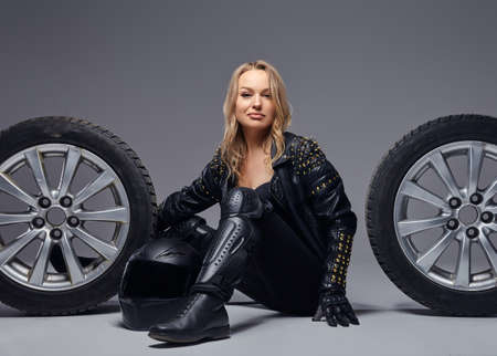 Sensual biker girl wearing motorcycle gear sitting on a floor with car wheels in a studio.