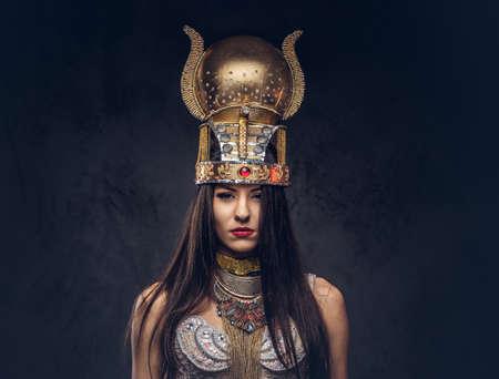 Porträt der hochmütigen ägyptischen Königin in einem alten Pharao-Kostüm. Auf dunklem Hintergrund isoliert. Standard-Bild