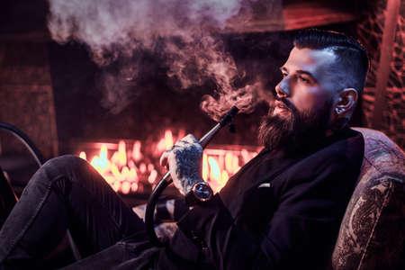 Porträt eines tätowierten bärtigen Mannes, der Wasserpfeife raucht und beim Chillen auf dem Sessel in der Nähe des Kamins schönen Dampf macht.