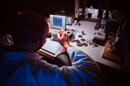 Mature watchmaker is working with WITSCHI ANALYZER Q1 at his own studio. 스톡 콘텐츠