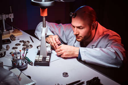 Mature watchmaker is doing engraving for custmers watch at his workshop. Stock Photo