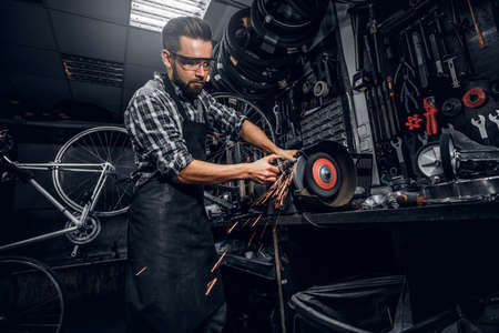 Skilled repairmaster is working with machine tool at busy bucycle workshop.